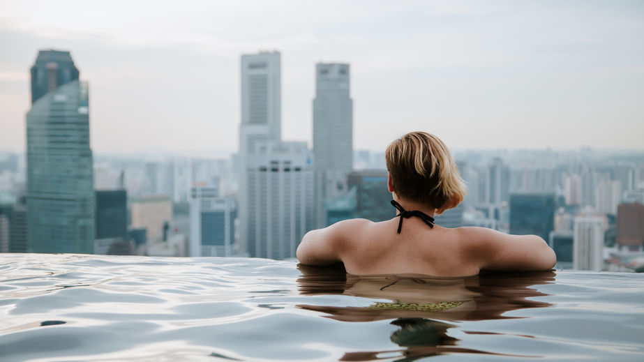 92741646 - woman in infinity swimming pool. business district aerial view. downtown landscape at golden sunset in marina bay
