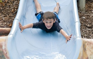 3705299 - adventurous boy comes down the slide head first