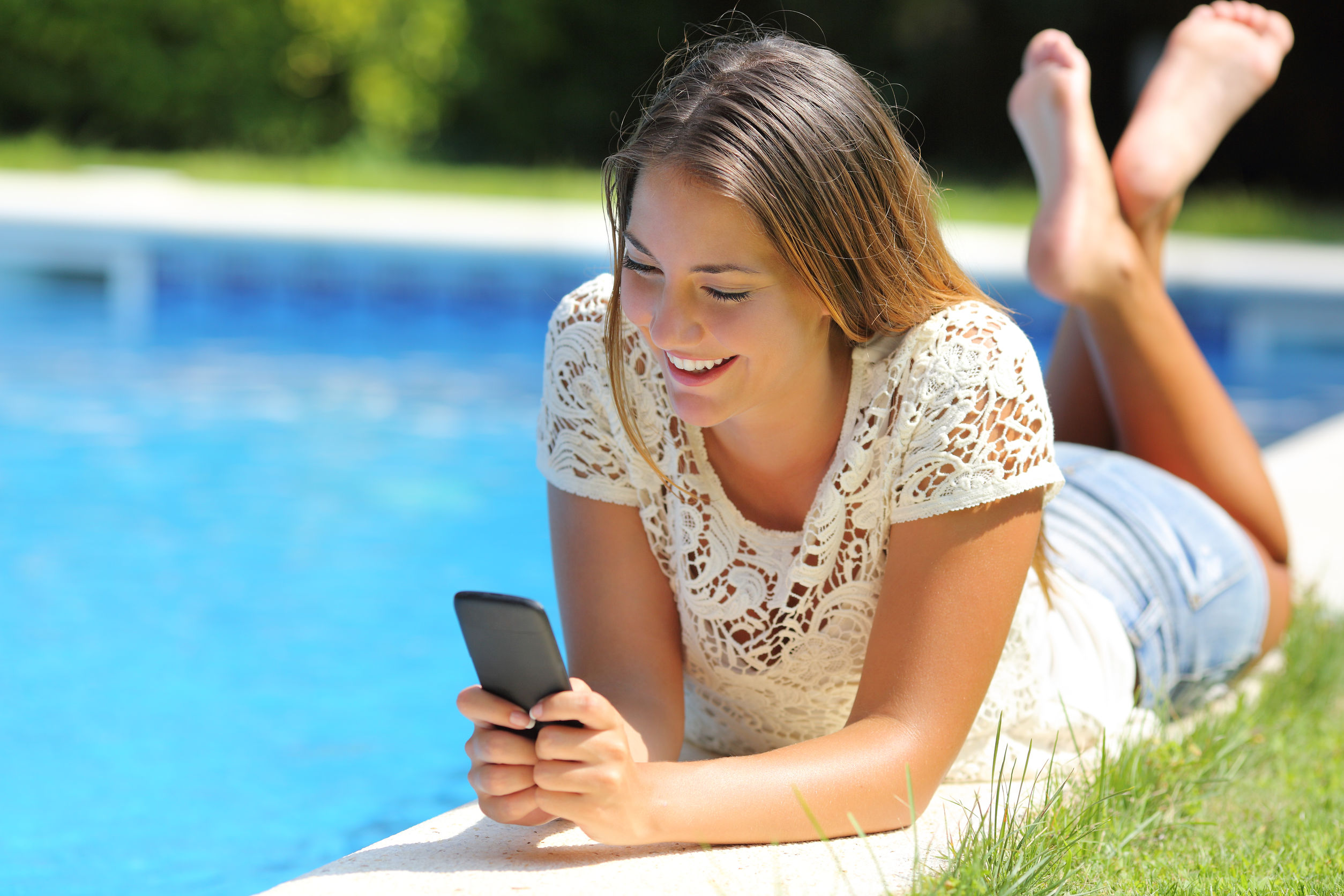 Teenager girl using a smart phone resting on a pool side with a blue water background