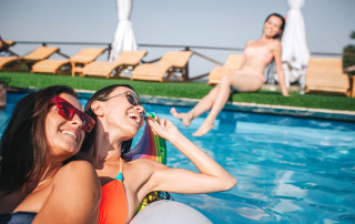 Picture of two model sitting together on float in swimming pool. They smile and look at third one. She sits at edge of water and splashing it. All of them have fun
