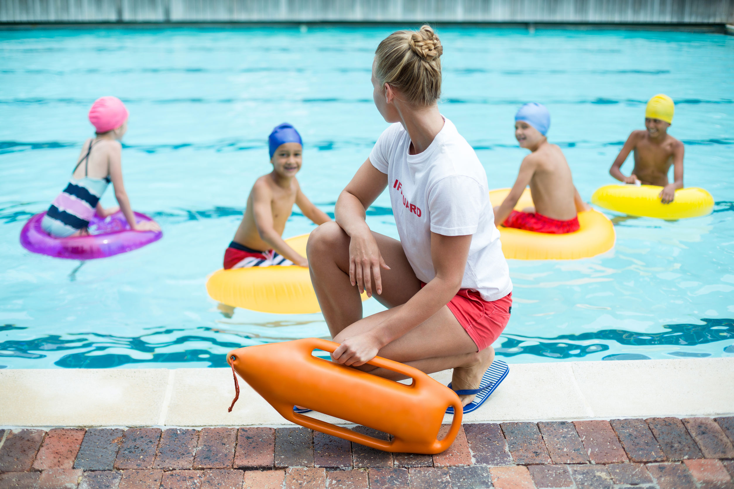 Female lifeguard holding rescue can while children swimming in pool
