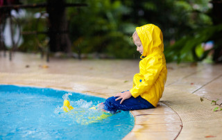 Kid jumping into swimming pool in rain. Child playing outdoors in tropical storm. Fun activities by summer rainy weather. Waterproof wear and footwear for kids. Children outdoors.