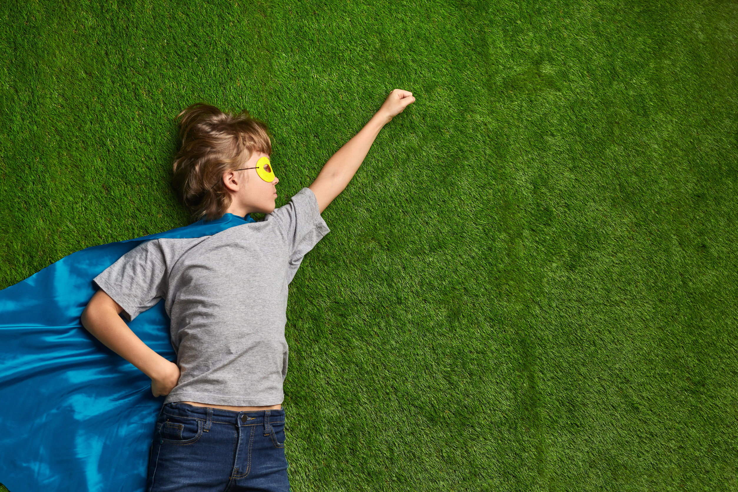 Little boy in superhero mask and cape lying in flying heroic pose against green grass