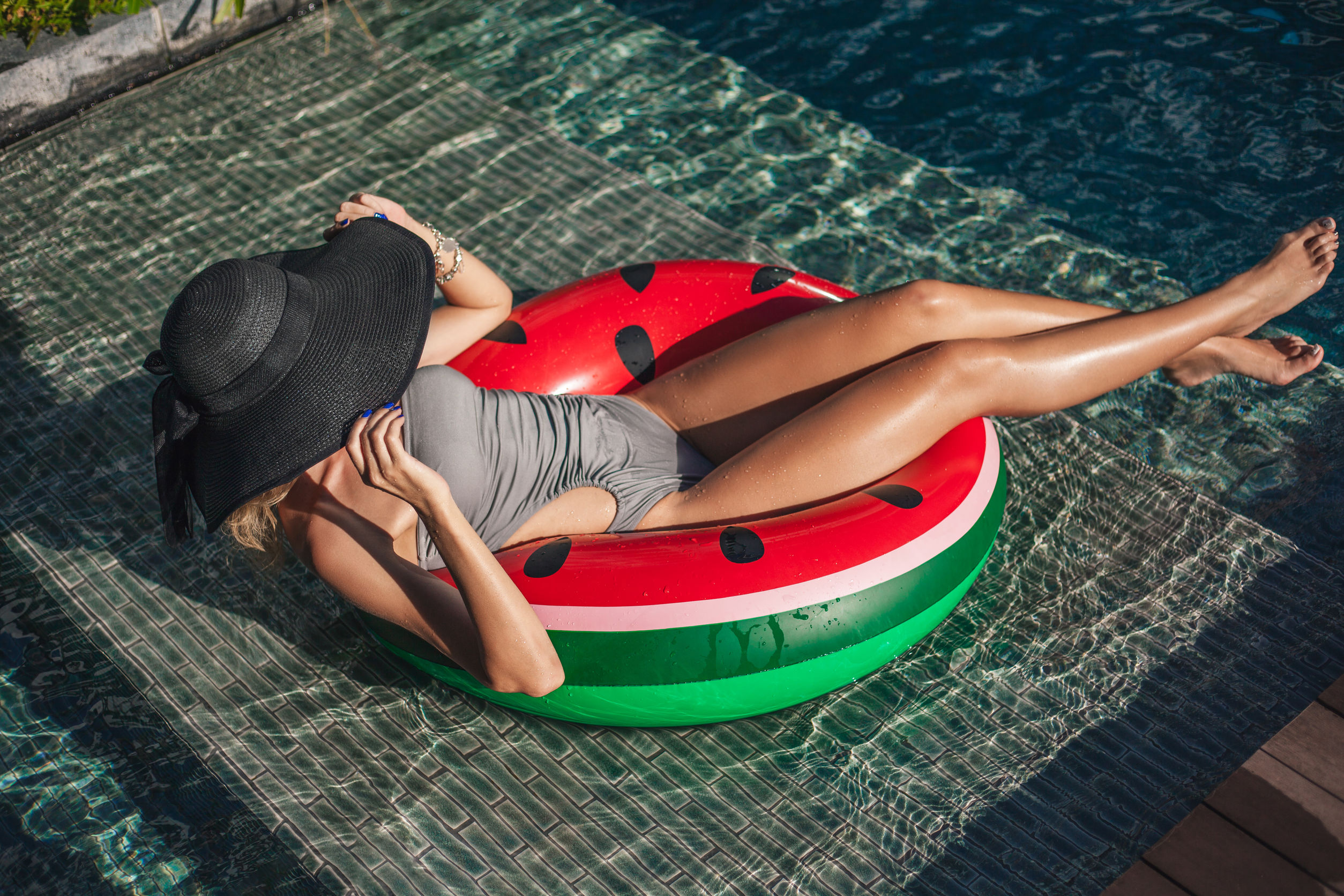 beautiful woman sitting in inflatable ring at poolside of hotel
