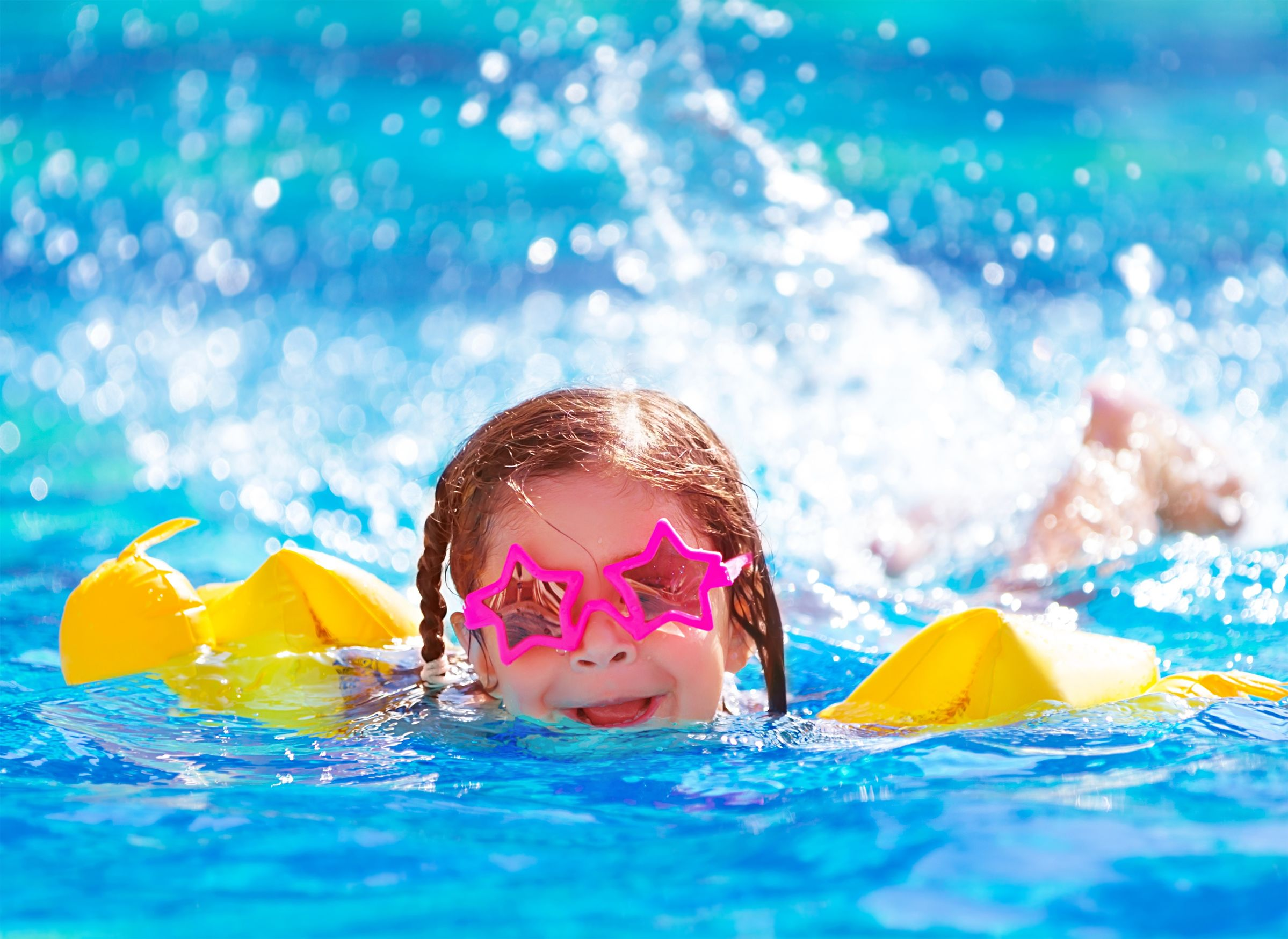 20772618 - closeup portrait of cute little arabic girl swimming in the pool, happy child having fun in water, beach resort, summer vacation and holidays concept