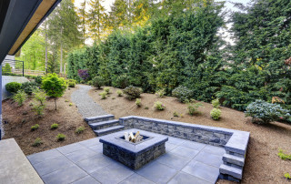 New modern home features a backyard with rectangular concrete fire pit framed by slate pavers and overlooking the lush garden. Northwest, USA