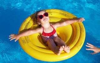 10229312 - funny little girl swims in a pool in an yellow life preserver