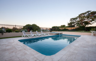 61899959 - blue water pool of a modern house or hotel with a garden with trees and fence around, the floor is made gray color tiles.
