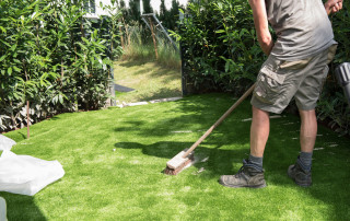 60098675 - professional gardener puts sand on artificial turf