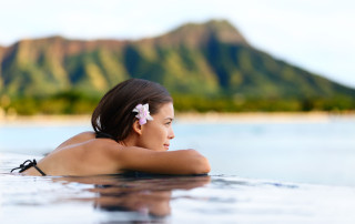 37149242 - infinity pool resort woman relaxing at sunset overlooking waikiki beach in honolulu city, oahu island, hawaii, usa. wellness and relaxation concept for summer vacations.