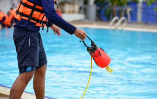 a man lifeguard training use throw bag rescue for help drowning case