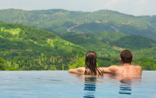 Rear view of happy couple in the pool looking at the mountain landscape. Travel, happiness emotion, summer holiday concept.